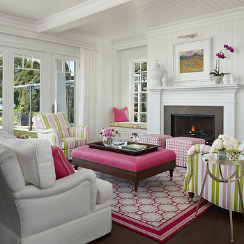Marianne Jones - living rooms - colorful living room, pink and green living room, cottage living room, wall of windows, floor to ceiling windows, beadboard ceiling, living room beadboard ceiling, beadboard living room ceiling, white beadboard ceiling, beadboard walls, white beadboard walls, traditional fireplace, fireplace mantel, glossy white canisters, fireplace alcoves, built in window seat, built in media cabinet, flatscreen tv, living room tv, pink ottomans, white and pink ottomans, cube ottomans, pink cube ottomans, white and pink cube ottomans, striped chairs, pink and green chairs, pink and green striped chairs, hot pink ottoman, ottoman coffee table, geometric rug, pink rug, pink geometric rug, white and pink geometric rug, white sofa, pink and green pillows,