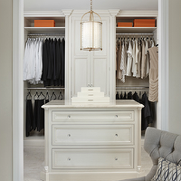 Marianne Jones - closets - walk in closet, closet design, walk in closet design, chic closet, classy closet, floor to ceiling built ins, closet built ins, walk in closet built ins, clothes organized by color, hermes, hermes orange, hermes box, hermes orange box, closet island, closet lighting, closet chandelier, antique brass chandelier, cage chandelier, brass cage chandelier, marble closet island, marble top closet island, cream lacquer box, stacked lacquer boxes, marble tile floor, gray chair, tufted chair, gray tufted chair,