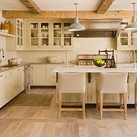 Scarp Ridge Lodge - kitchens - L shaped kitchen, rustic country kitchen, country kitchen, country lodge kitchen, cream cabinets, cream kitchen cabinets, glass cabinets, glass front cabinets, glass front upper cabinets, cream base cabinets, cream lower cabinets, upper cabinets, lower cabinets, gray countertops, perimeter countertops, gray perimeter countertops, subway tile, subway tile backsplash, cream kitchen island, kitchen island, dual prep sinks, kitchen with 2prep sinks, kitchen island with 2 sinks, 2 sinks in kitchen island, dual kitchen island sinks, gray pendants, gray lanterns, gray kitchen island lanterns, barn pendants, vintage barn pendants, gray barn pendants, vintage gray pendants, upholstered bar stools, upholstered barstools, upholstered counter stools, gray washed floor, rustic stool,