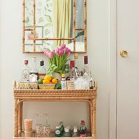 Matchbook Magazine - dining rooms - Sherwin Williams - Enlightened Lime - handwoven bar cart, rattan bar cart, handwoven rattan bar cart, libations, bamboo mirror, gold bamboo mirror, gold faux bamboo mirror, light green walls, light green paint, light green paint color, striped rug, white and pink rug, white and pink striped rug, south seas bar cart,