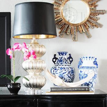 Little Green Notebook - living rooms - chic vignette, chic living room, glamorous vignette, vignette on media cabinet, black media cabinet, glossy black media cabinet, vignette, small pink orchid, pink orchid, mercury glass table lamp, mercury glass lamp, black lampshade with gold interior, black and gold lampshade, stacked books, antler, blue and white vases, gray wall color, gray walls, soft gray walls, gold sunburst mirror, sunburst mirror,