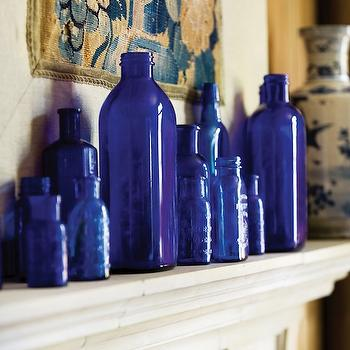 Atlanta Homes & Lifestyles - living rooms - limestone mantel, limestone fireplace, blue bottles, cobalt blue glass bottles, collection of antique cobalt blue bottles, antique tapestry, blue and white china vase, cobalt blue, cobalt blue bottles, cobalt blue vase,