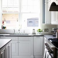 Rue Magazine - kitchens - kitchen with blue walls, beveled subway tile, kitchen beveled subway tile, beveled subway tile backsplash, beveled subway backsplash, beveled subway tile kitchen backsplash, inset cabinets, white inset cabinets, white kitchen cabinets, black countertops, black kitchen countertops, honed countertops, honed kitchen countertops, kitchen sink, bank of windows, hand scraped floors, hand scraped wood floors, wide plank floors, wide plank wood floors, eclectic accents, kitchen accents, eclectic kitchen accents,