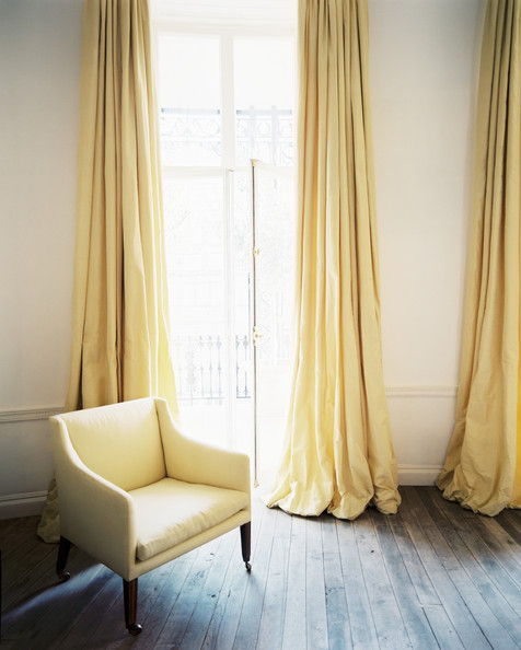 Lonny Magazine - living rooms - ivory walls, ivory wall color, hardwood floors, unfinished hardwood floors, wall molding, yellow chair, pale yellow chair, yellow drapes, yellow curtains, pale yellow drapes, pale yellow curtains, french doors, yellow window panels,