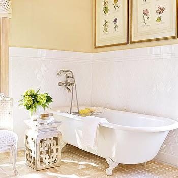 BHG - bathrooms - diamond patterned tile, diamond shaped tile, white diamond shaped tile, honey colored floor tile, white cast iron tub, cast iron bath, cast iron claw foot bath, cast iron claw foot tub, polished nickel wall mounted faucet, wall mounted faucet, wall mounted faucet and shower head, fretwork garden stool, garden stool, vintage chair, tiled bathroom, tiled bathroom floors, soft yellow walls, yellow wall color, vintage botanical prints, vintage framed botanical prints, yellow bathroom, tiled wainscoting, diamond tile, diamond tile backsplash, diamond backsplash,