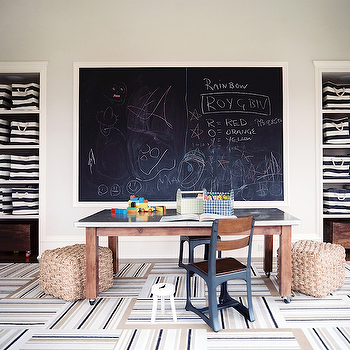 Lonny Magazine - boy's rooms: playroom, playroom with vaulted ceilings, vaulted ceilings, gray wall color, chalkboard, framed chalkboard, chalk board, large chalkboard, kids room with chalkboard, hardwood floors, open shelving, recessed open shelving, black and white striped canvas storage, canvas storage, woven poufs, pouf, industrial chairs, wood and metal chair, metal topped table, metal topped desk, wood desk with metal top, desk on castors, removable floor tiles, striped floors tiles, neutral striped floor tiles, striped carpet tiles, carpet tiles,