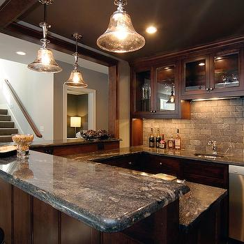 Rubble Tile - basements - basement wet bar, wet bar, glass front cabinets, upper cabinets, glass front upper cabinets, wet bar cabinets, stained cabinets, chocolate brown cabinets, marble countertops, black marble, black marble countertops, raised bar, raised marble bar, leather bar stools, brown leather bar stools, nailhead bar stools, nailhead leather bar stools, staggered tile, staggered tile backsplash, wood paneled wet bar, bell jar pendants, mercury glass pendants, mercury glass bell jar pendants,