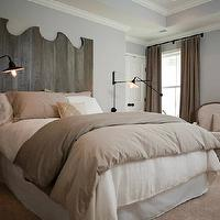 Sabal Homes SC - bedrooms - beautiful bedroom, gray walls, gray bedroom walls, rustic plank headboard, carved wood headboard, plank headboard, driftwood headboard, queen bed, pink and gray bedding, pink and gray duvet, pink and gray shams, iron sconces, iron swing arm sconces, oval nightstands, glass nightstands, oval glass nightstand, floor to ceiling curtains, taupe curtains, taupe drapes, taupe window panels, upholstered chair, gold garden stool, reclaimed wood headboard,