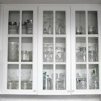 Grace Happens - kitchens - glass font cabinets, glass front kitchen cabinets,  Kitchen with glass-front cabinets filled with glassware.
