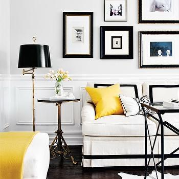 Style at Home - living rooms - gray walls, light gray walls, pale gray walls, wainscoting, wall paneling, wall moldings, wainscoting paneled walls, skirted sofa, white skirted sofa, black white and yellow room, black white and yellow living room, directorie table, black directorie table, black and white cowhide rug, cowhide rug, cowhide, hide rug, white ottoman, yellow throw, yellow fringed throw, yellow pillow, bright yellow pillow, brass side table, ornate brass side table, brass floor lamp, brass floor lamp white black shade, gallery wall, art wall, art collection, black and gold framed art, white pillow with black piping, white sofa with black ribbon trim, white sofa with black banded skirt, white sofa with pleated skirt, white sofa with black trim, black and yellow living room, white black and yellow living room,