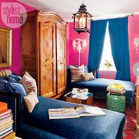 Style at Home - living rooms - bright pink living room, hot pink living room, hot pink walls, bright pink walls, hot pink wall color, bright pink wall color, blue drapes, royal blue drapes, cobalt blue drapes, white wall sconces, white double wall sconces, antique armoire, mirrored accent table, emerald green and gold giraffe print stool, traditional rug, black pagoda lantern, pagoda lantern pendant, gold framed oil painting, stacked books, multi-colored striped pillow, leopard print pillow, bold living room, colorful living room, eclectic living room, blue velvet chaise, chaise lounge, blue velvet chaise lounge, navy blue velvet chaise, pink and blue living room, blue curtains, cobalt blue curtains, indigo blue, indigo blue chaise lounge,