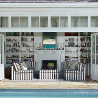 Tim Barber - pools - pool house, california pool house, white siding, siding, gray tiled roof, slate tiled roof, gray slate tiled roof, fireplace, built-in bookshelves, bookshelves flanking fireplace, gray and white striped sofa, striped sofa, gray and white striped ottoman, striped ottoman, bi fold doors, bi fold exterior doors, pool house doors, bi fold glass paned doors, transom window, pool house with bi fold doors, lanterns, outdoor lanterns,