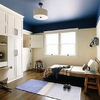 Simo Design - boy&#039;s rooms - boys bedroom, navy blue ceiling, navy blue painted ceiling, dark blue ceiling, dark blue painted ceiling, drum pendant, drum pendant with diffuser, hardwood floors, built-ins, built-in closet, built-in storage, built-in bedroom storage, white bedding, white bed linens, built-in desk, built-in workstation, ivory walls, ivory wall color, rustic nightstand, rustic side table, grid patterned throw, grid throw, blue rug, globe, zebra bust, Eames Eco Chic Modern Rocker, , built in desk, boys built in desk, zebra head,