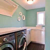 Refined LLC - laundry/mud rooms - tiffany blue, tiffany blue laundry room, espresso floor tile, laundry room, front loading washer, silver front loading washer, front loading dryer, silver front loading dryer, folding counter, folding counter in laundry room, tiffany blue walls, flat paneled cabinets, white cabinets, white cabinetry, shelf with drying rail, white round mirrors, sink, sink in laundry room, small laundry room, compact laundry room, organized laundry room, ceiling mount pendant, flush mount pendant, white counter, white countertop,