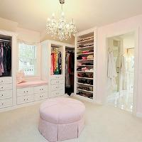 Refined LLC - closets - pink closet, pink walk-in closet, pink walls, pink wall color, baby pink walls, baby pink wall color, wall to wall carpet, natural fiber carpet, natural fiber carpeting, pink pleated ottoman, round pink pleated skirt ottoman, window seat, window seat in closet, closet system, closet storage, walk-in closet, master closet, crystal chandelier, shoe storage, clothes storage, built-in closet, clothes rails, drawer storage,