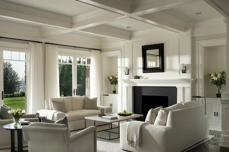 Shope Reno Wharton - living rooms - monochromatic living room, cream living room, white living room, wall of french doors, living room french doors, wall of transom windows, living room transom windows, wall of french doors and transom windows, floor to ceiling curtains, white curtains, white drapes, coffered ceiling, fireplace alcoves, built ins, built in cabinets, living room built ins, living room built in cabinets, fireplace cabinets, built in fireplace cabinets, alcove cabinets, fireplace alcove cabinets, black and white fireplace, fireplace mirror, black fireplace mirror, cream sofa, modern sofa, modern cream sofa, marble top coffee table, cream rug, cream velvet chair,