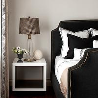 Amy Meier Design - bedrooms - putty colored wall, putty wall color, hardwood floors, dark hardwood floors, black velvet bed, black velvet headboard with nailhead trim, black velvet headboard, black velvet pillow, white bedding with black border, antique brass nailhead trim, brass nailhead trim, white cube side table, white cube table, brass and glass lamp, glass lamp with brass trim, antique brass and glass lamp, cane patterned shade, pedestal vase, white flowers, greek key drapes, drapes with greek key trim, greek key curtains, curtains with greek key trim, black bed, black velvet bed, black and white bedding, cashmere throw, camel throw blanket, camel cashmere throw, nailhead headboard, studded headboard, black studded headboard, cube nightstand, white nightstand, white cube table, white lacquer table, white lacquer cube, white lacquer cube table,