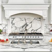 Bradford Designs - kitchens - formal kitchen, formal white kitchen, white on white kitchen, all white kitchen, white kitchen, traditional kitchen, traditional white kitchen, white kitchen cabinets, white kitchen cabinetry, marble counters, marble countertops, calacatta marble, calacatta marble counters, calacatta marble countertops, crystal knobs, crystal hardware, french style kitchen, white french style kitchen, oven hood, custom hood, paneled hood, hood with corbel supports, seamless backsplash, marble backsplash, calacatta marble backsplash, white oven, white range, white oven range, custom oven hood, grand oven hood, large white oven hood, kitchen island, kitchen island sink, formal kitchen island, undermount sink, undermount stainless steel sink, gooseneck faucet, marble veining,
