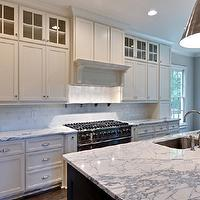 Blake Shaw Homes - home exteriors - white cabinetry, white cabinets, glass front cabinets, glass fronted cabinetry, glass fronted accent cabinets, ceiling height cabinetry, crown molding recessed lighting, white kitchen cabinets, white kitchen cabinetry, marble counters, marble countertops, under cabinet lighting, white subway tile, subway tile, subway tiled backsplash, white subway tiled backsplash, marble topped island, kitchen island with sink, sink in kitchen island, undermount sink, stainless steel sink, gooseneck faucet, recessed lighting, pot lights, silver pendants, silver kitchen pendants, cone shaped kitchen pendants, double hung windows, stainless steel oven, stainless steel ledge, paneled oven hood, sash windows, double hung sash windows, Goodman Hanging Lamps in Antique Nickel,