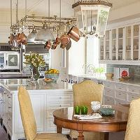 Christine Markatos Design - kitchens - eat in kitchen, country kitchen, chic country kitchen, glass front kitchen cabinets, white kitchen cabinets, marble countertops, blue subway tile, blue subway tile backsplash, kitchen island pot rack, stainless steel pot rack, kitchen island storage, kitchen island sink, copper pots and pans, prep sink, island prep sink, eat in kitchen, glass lantern, dining room lantern, round dining table, yellow dining chairs, slipcovered chair, yellow slipcovered chair, camelback chair, yellow camelback chair, camelback slipcovered chair, slipcovered camelback chair,