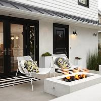 K Mathiesen Brown Design - porches - white and black home exterior, semi-covered porch, black door, black front door, black door moldings, outdoor fire pit, fire pit, white outdoor chairs, trina turk pillows, paradise print, paradise print pillows, paradise print driftwood pillows, contemporary porch, yellow and gray pillows, houndstooth pillow, yellow and gray houndstooth pillow,