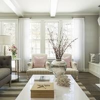 Martha O'Hara Interiors - living rooms - gray and pink living room, gray and pink family room, hardwood floors, patio doors, double hung windows, sash windows, double hung sash windows, sheers, white sheers, gray walls, gray wall color, contemporary fireplace, contemporary fireplace surround, tv over fireplace, flat screen over fireplace, candlesticks, glossy white coffee table, white coffee table, silver vase, vase of branches, coral, starfish, wooden box, striped rug, gray and white striped rug, gray and ivory striped rug, contemporary gray sofa, tufted gray sofa, contemporary tufted gray sofa, pink and white striped pillow, dark gray pillow, pink pillow, beams, white beams, recessed lighting, pot lights, marble side table, antiqued gold and marble side table, silver lamp, tall silver lamp, built-in bench, built-in bench next to fireplace, patio doors, pink and gray color scheme, pink and gray interiors, club chairs, striped club chairs, pink pillows, living room arrangement, gray sofa, gray tufted sofa, high back sofa, gray high back sofa,