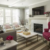 Martha O'Hara Interiors - living rooms - gray and pink living room, gray and pink family room, hardwood floors, patio doors, double hung windows, sash windows, double hung sash windows, sheers, white sheers, gray walls, gray wall color, contemporary fireplace, contemporary fireplace surround, tv over fireplace, flat screen over fireplace, candlesticks, glossy white coffee table, white coffee table, silver vase, vase of branches, coral, starfish, wooden box, striped rug, gray and white striped rug, gray and ivory striped rug, contemporary gray sofa, tufted gray sofa, contemporary tufted gray sofa, pink and white striped pillow, dark gray pillow, pink pillow, beams, white beams, recessed lighting, pot lights, marble side table, antiqued gold and marble side table, silver lamp, tall silver lamp, built-in bench, built-in bench next to fireplace, patio doors, pink and gray color scheme, pink and gray interiors, club chairs, striped club chairs, pink pillows, living room arrangement, pink chair, dark pink chair, pink wing chair,