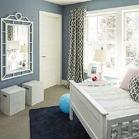 Martha O'Hara Interiors - girl's rooms: girls bedroom, blue walls, blue wall color, blue girls bedroom, wall to wall carpeting, navy blue rug, dark blue rug, solid navy rug, angled bed, white bed, girls bed, ruffled white duvet, pink pillow, ivory pillow, dog print pillow, fretwork pillow, gray and white fretwork pillow, floor length drapes, floor length curtains, gray and white fretwork drapes, gray and white fretwork curtains, double hung windows, sash windows, double hung sash windows, acrylic nightstand, white lamp, garden stools, white ceramic garden stools, glazed white ceramic garden stools, whale wallpaper, Summer Palace Fret on Smoke, Little Whales Wallpaper in Charcoal on White, Chloe Mirror, corner bed,
