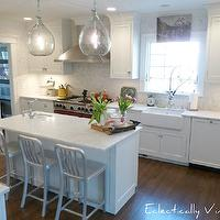 Eclectically Vintage - kitchens - Sherwin Williams - Nebulus White - white kitchen, white kitchen cabinets, white cabinets, white kitchen cabinetry, white cabinetry, polished nickel hardware, kitchen island, kitchen island with sink, undermount sink, marble counters, marble countertops, honed carrara marble counters, honed carrara marble countertops, hardwood floors, ceiling height cabinetry, shaker cabinets, white shaker cabinets, demijohn pendants, demijohn lights, herringbone marble mosaic backsplash, herringbone patterned marble backsplash, ceiling height backsplash, stainless steel stove, stainless steel oven, stainless steel hood, farm sink, farmhouse sink, apron sink, spray faucet, modern spray faucet, kitchen window, herringbone backsplash, recessed lighting, pot lights, Delta Barstools Crate and Barrel, honed carrara marble, nebulous white,