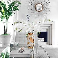 Paper City - living rooms - white living room, silver sunburst mirror, modern fireplace, fireplace mirror, glass and nickel coffee table, white and gold vase, barcelona chair, white barcelona chair, gray rug,