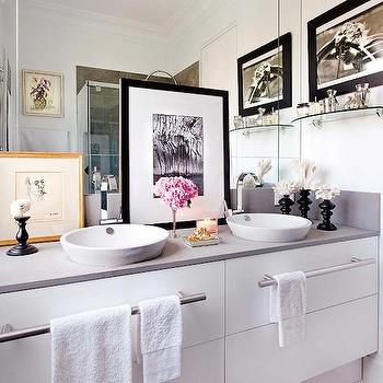 Nuevo Estilo - bathrooms - chic bathroom, modern white vanity, modern white sink vanity, modern white double sink vanity, his and hers sinks, master bathroom, brushed nickel towel bars, towel rails, vessel sink, white vessel sink, gooseneck faucet, polished chrome gooseneck faucet, mirrored backsplash, mirrored vanity wall, layered art, framed layered art, glass shelf, gray counters, gray countertops, crown molding, recessed lighting, pot lights, his and her sinks, his and her vessel sinks,