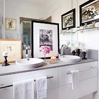 Nuevo Estilo - bathrooms - chic bathroom, modern white vanity, modern white sink vanity, modern white double sink vanity, his and hers sinks, master bathroom, brushed nickel towel bars, towel rails, vessel sink, white vessel sink, gooseneck faucet, polished chrome gooseneck faucet, mirrored backsplash, mirrored vanity wall, layered art, framed layered art, glass shelf, gray counters, gray countertops, crown molding, recessed lighting, pot lights, his and her sinks, his and her vessel sinks,
