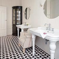 Nuevo Estilo - bathrooms - black and white marble floor, black and white marble tiled floor, black white and gray marble floor, black white and gray marble tiled floors, pedestal sinks, white pedestal sinks, linen club chair, grainsack club chair, round mirror, frameless round mirror, wall sconces, bathroom sconces, ivory walls, ivory wall color, paneled walls, wood paneled walls, painted wood paneled walls, corner cabinet, corner display cabinet, glass fronted corner display cabinet, Parisian Pedestal Sink,
