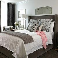 Jane Lockhart Interior Design - bedrooms: gray bedroom, gray bed, gray upholstered wing back bed, wing back bed, white bedding, white bed linens, gray blossom pillows, gray striped pillows, gray branch pillows, silver framed art, crystal table lamp, floor lamp, round nightstand, black nightstand, mismatched nightstand, gray throw, chunky knit throw, pink shawl, pink throw, charcoal gray drapes, charcoal gray curtains, gray walls, gray wall color, antiqued mirror, printmakers sideboard, upholstered chair, hounds tooth chair, hounds tooth upholstered chair, geometric gray pillow, Dwell Studio Vintage Blossom Dove Shams, Dwell Studio Charcoal Lumbar pillow, Dwell Studio Gate Charcoal Pillow,