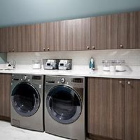 Jane Lockhart Interior Design - laundry/mud rooms - modern laundry room, contemporary laundry room, contemporary cabinets, contemporary cabinetry, veneer cabinet fronts, veneer slab cabinet doors, light stone counters, light stone countertops, built-in washer, built-in dryer, silver front loading washing machine, silver front loading dryer, mini white subway tile, mini white subway tiled backsplash, light tiled floors, green blue walls, green blue wall color, prep sink, veneer cabinets, modern veneer cabinets, laundry room cabinets, laundry room,