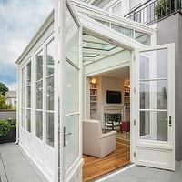 Sutro Architects - home exteriors - sunroom, sunroom extension, garden room, garden room extension, conservatory, conservatory extension, concrete tiled patio, concrete patio, hardwood floors, natural stone fireplace, built-ins, built-in bookshelves, terrace, gray exterior, gray painted exterior, gray exterior paint,