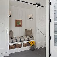 Wendy Posard - laundry/mud rooms - sliding barn doors, white barn doors, sliding white barn doors, hidden mud area, hidden mud room, bench, built-in bench, bench with built-in storage, woven baskets, cubbies, basket cubbies, striped gray and blue bench cushion, gray pillows, iron wall sconces, double iron wall sconces, paneled walls, wood paneled walls, tongue and groove wood paneled walls, white wood paneling, white wood paneled walls, gray tiled floors, matte gray tiled floors, oversized gray tiled floors, double french doors, watering can, galvanized watering can,