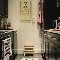The Every Girl - kitchens - galley kitchen, black galley kitchen, black cabinets, black kitchen cabinets, glossy black cabinets, glossy black kitchen cabinets, white marble, white marble countertops, black cabinets with white marble counters, black cabinets with white marble countertops, black kitchen cabinets with white marble counters, black kitchen cabinets with white marble countertops, eye chart art, you are so beautiful art, step stool, vintage step stool, kitchen step stool, geometric runner, white and blue runner, kitchen runner, kitchen rug, geometric kitchen runner, white and blue geometric runner, white and blue geometric rug,