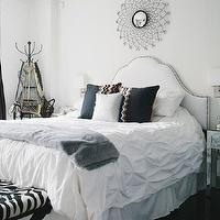 The Every Girl - bedrooms - chic bathroom, studded headboard, white headboard, white studded headboard, studded white headboard, white headboard with nailhead trim, white headboard with silver nailhead tray, black pillows, faux fur throw, gray faux fur throw, mirrored nightstands, zebra ottomans, zebra stools, mirror over bed, mirror above bed, mirror above headboard, mirror over headboard,