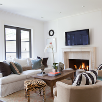 Ashley Goforth Design - living rooms - slipcovered sofa, white slipcovered sofa, white sofa, mitered pillows, tan mitered pillows, white and tan pillows, white and tan mitered pillows, blue pillows, blue velvet pillows, greek key trim pillows, reclaimed wood coffee table, salvaged wood coffee table, coral rug, persian rug, coral persian rug, tiger ottoman, fireplace alcoves, stone fireplace, fireplace tv, tv fireplace, black convex mirror, gallery frame, white gallery frames, barrel back chairs, black and white pillows, black and white striped pillow, blue garden stool,