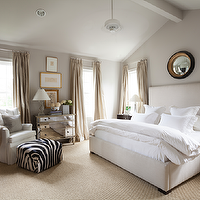 Ashley Goforth Design - bedrooms - vaulted ceiling, vaulted ceiling bedroom, bedroom vaulted ceiling, high vaulted ceiling, black and gold convex mirror, mirror over bed, mirror over headboard, mirror above bed, mirror above headboard, pinch pleat curtains, pinch pleat drapes, champagne curtains, silk champagne curtains, nightstand in front of window, curved nightstand, espresso nightstand, curved espresso nightstand, tall headboard, off white headboard, off white bed, upholstered headboard, upholstered bed, bedroom ceiling fan, ceiling fan bedroom, sisal rug, wall to wall sisal rug, gray walls, soft gray bedroom walls, white wingback chair, wingback chair, white tufted chair, tufted wingback chair, wingback tufted chair, white tufted wingback chair, white wingback tufted chair, zebra ottoman, mirrored chest, Amelie Mirrored Hall Chest,