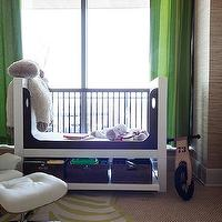 Sweet boy's nursery design with tan raffia wallpaper paired with green curtains framing ...