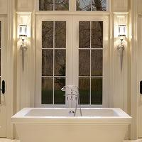 Parkyn Design - bathrooms - rectangular bath, soaking tub, freestanding tub, rectangular tub, freestanding bath tub, floor mounted faucet, french doors, french doors in bathroom, french doors with transom windows, arched doorway, arched patio doors, mill work, moldings, traditional mill work, torchiere sconces, contemporary torchiere sconces, limestone tiled floors, limestone floor tile, limestone bathroom floors, bath in front of windows, bath in front of french doors, traditional bathroom, rectangular pedestal bathtub, rectangular pedestal bath, tub in front of window, bathtub in front of window,