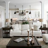 Staples Design Group - living rooms: open plan, open concept, open concept kitchen, open concept family room, open plan kitchen, open plan family room, hardwood floors, dark hardwood floors, recessed lighting, pot lights, slipcovered dining chairs, slipcovered parsons chairs, coffee table, dark stained coffee table, candlesticks, traditional rug, traditional blue and beige rug, rolled arm sofa, rolled arm settee, french pillows, single drawer side table, mercury glass lamp, white orchid, greige walls, greige wall color, armchair, armchair with matching ottoman, rolled arm chair, breakfast area, breakfast nook off kitchen, white kitchen, white kitchen cabinets, kitchen island, black counters, black countertops, white kitchen cabinetry, oil-rubbed bronze pendants, dark stained side tables, family room, neutral family room, columns, column supports,