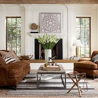 Staples Design Group - living rooms - brown sofa, brown settee, chocolate brown sofa, chocolate brown velvet sofa, brown velvet sofa, brown velvet rolled arm sofa, rolled arm settee, rolled arm chair, brown velvet pillow, textured brown pillow, zebra print pillow, iron based wood topped coffee table, leather tripod stool, tripod stool, woven rug, jute rug, natural fiber rug, layered rugs, black white and gray striped rug, striped rug, woven tray, tall vase, gladiolas, chocolate brown armchair, brown velvet armchair, garden stool, interlocking circle garden stool, raised fireplace, elevated fireplace, transitional fireplace, tall windows, windows flanking fireplace, framed geometric art print, framed geometric art, shell fossil on plinth, fossilized shell, white walls, white throw, beamed ceilings, exposed beam ceilings, wood beamed ceilings, neutral living room,
