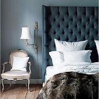 bedrooms: chic bedroom, smoky blue, smoky blue walls, smoky blue bedroom walls, blue bedroom walls, tall headboard, tall blue headboard, blue headboard, tall blue headboard, blue velvet headboard, blue tufted headboard, blue wingback headboard, blue velvet tufted headboard, blue velvet wingback headboard, blue velvet tufted wingback headboard, velvet tufted wingback headboard, greek key bedding, faux fur throw, faux fur throw blanket, swing arm sconce, bedroom sconce, french chair, upholstered french chair, rustic plank floor, plank floor, chic french bedroom,