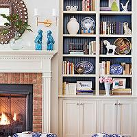 BHG - living rooms - built ins, built in cabinets, living room built ins, living room built in cabinets, fireplace cabinets, fireplace built in cabinets, built in bookshelves, fireplace bookshelves, living room bookshelves, fireplace built in bookshelves, living room built in bookshelves, beadboard bookcase, blue beadboard bookcase, beadboard built ins, beadboard built in cabinets, blue beadboard built ins, fireplace alcoves, peacock mirror, fireplace mirror, turquoise foo dogs, turquoise blue foo dogs. brass double sconce, fireplace sconce, recycled glass vase, brick fireplace, brick fireplace surround, red brick fireplace surround, dentil molding, fireplace dentil molding, kalah blue ottomans, tufted ottomans, white and blue ottomans, white and blue ikat ottomans, ikat ottomans, ikat tufted ottomans,