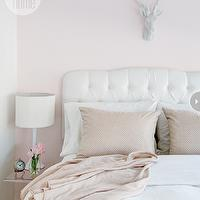Style at Home - bedrooms: white and pink bedroom, pink bedroom, pale pink walls, light pink walls, pale pink bedroom walls, light pink bedroom walls, white deer head, white headboard, white tufted headboard, white velvet headboard, white velvet tufted headboard, white bedding, pink shams, acrylic table, acrylic nightstand, white table lamp, pink accents, bedroom pink accents, pink accents bedroom,