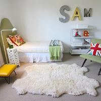 JAC Interiors - boy&#039;s rooms - white walls, kids bedroom, white shutters, shuttered windows, wall to wall carpeting, gray carpet, dove gray carpet, shag rug, green headboard, upholstered green headboard, arched green headboard, white bed skirt, white duvet, white pillow with green polka dots, vintage style pillow, multi-colored pillow, union jack pillow, british flag pillow, green chair, modern green chair, green fringed throw, modern white floor lamp, modern moroccan side table, white moroccan style side table, striped throw, metal framed white storage shelves, white woven baskets, wall letters, black bookshelves, black storage shelves, yellow stool, white and green boys room, white and green boys bedroom,