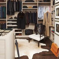 Elle Decor - closets - walk-in closet, walk-in wardrobe, master closet, master bedroom closet, closet island, hardwood floors, cowhide, cowhide rug, cream cowhide rug, clothes rails, open shelving, floor to ceiling storage, built-ins, contemporary chair, pull-out shoe storage, closet storage, organized closet, closet system, closet built-in, master bedroom walk-in closet, pull-out shoe trays, mens closet, mens walk in closet, mens walk in closet design,
